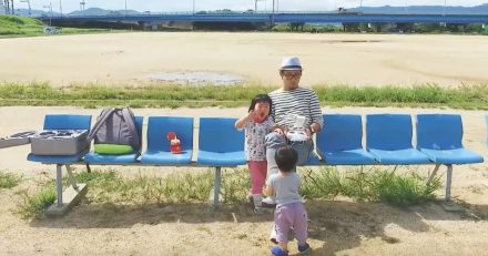 A little boy sitting on a bench