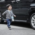 A young boy standing in front of a car